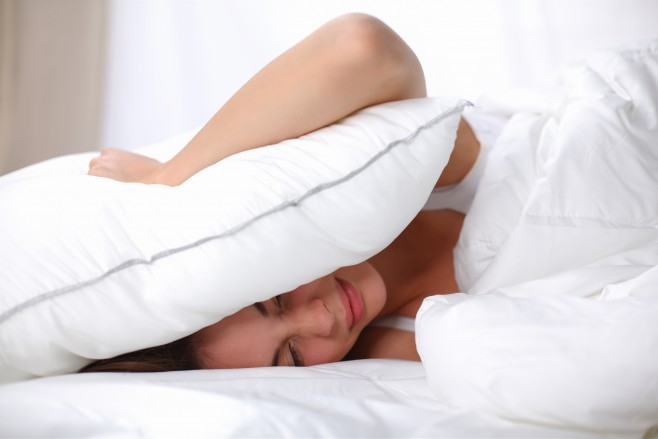 Female lying on bed and closing her ears with pillow, isolated